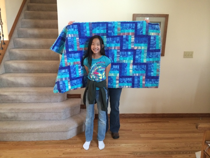 The quilt is folded over.  Barb's holding it behind Rachel.