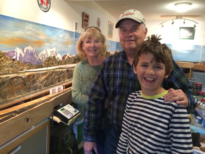 Lynda and Dave with Charlie next to Dave's model trains in their basement